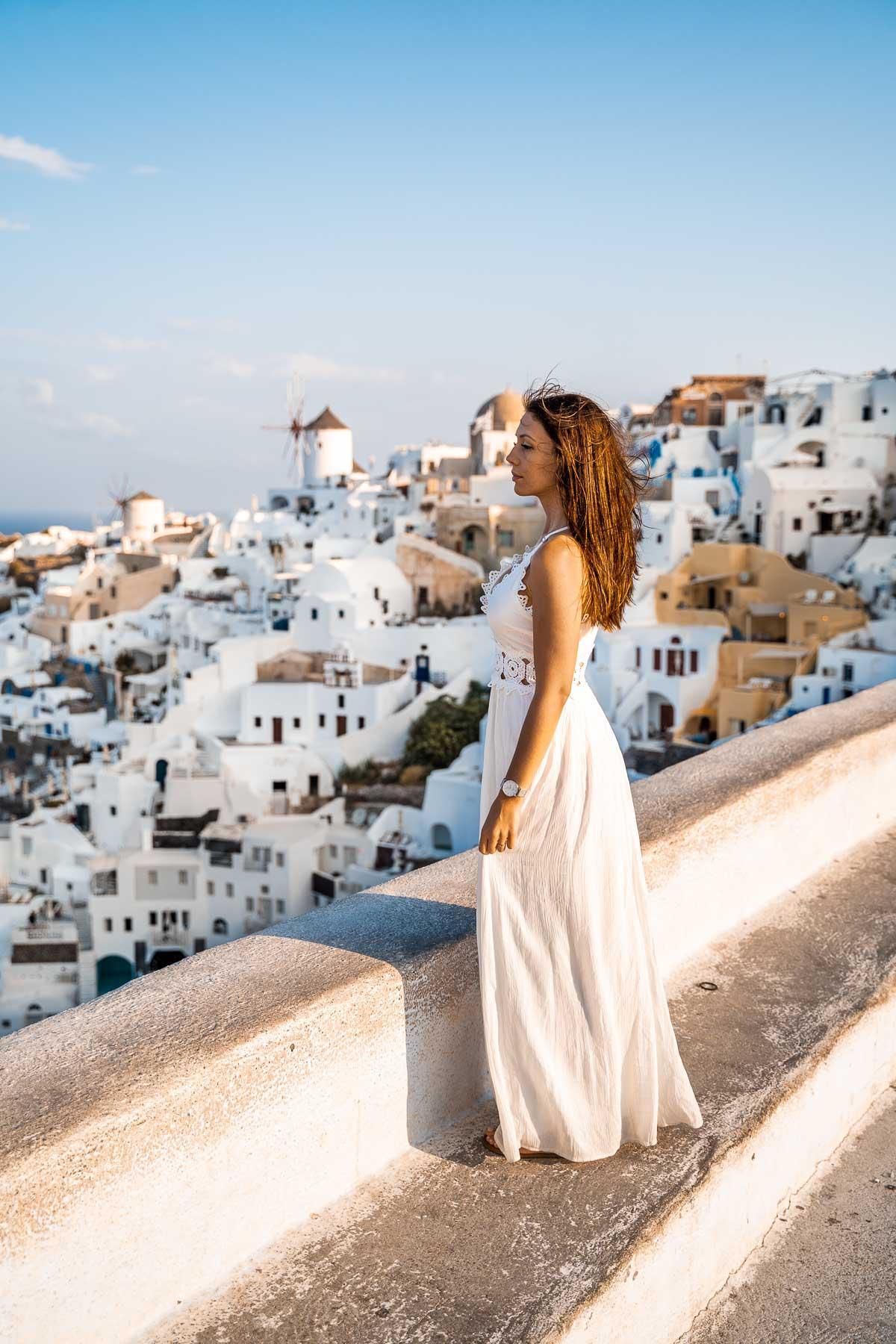 Girl in a white dress standing in the Oia Castle, Santorini