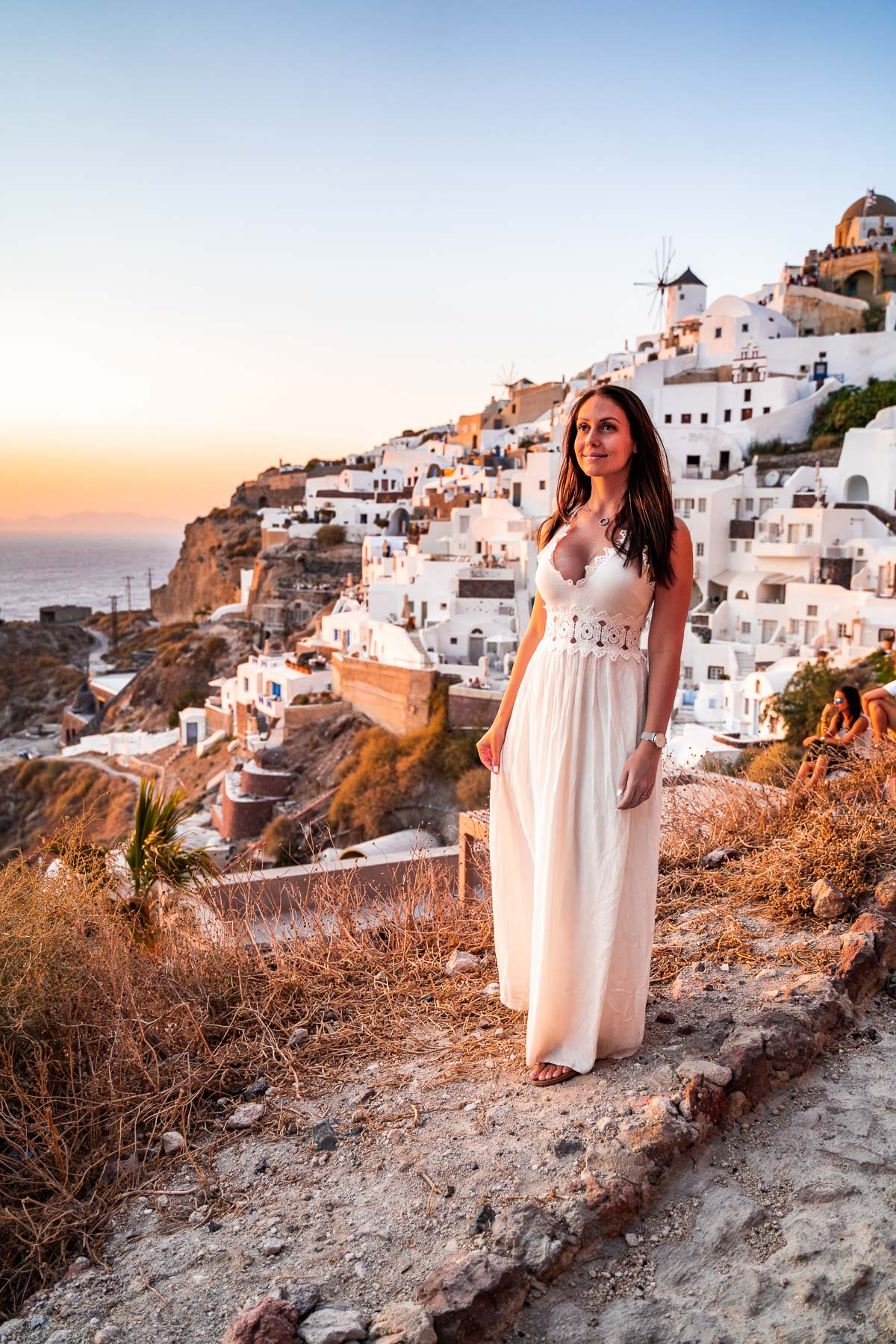 Girl in a white dress watching the sunset in Oia, Santorini