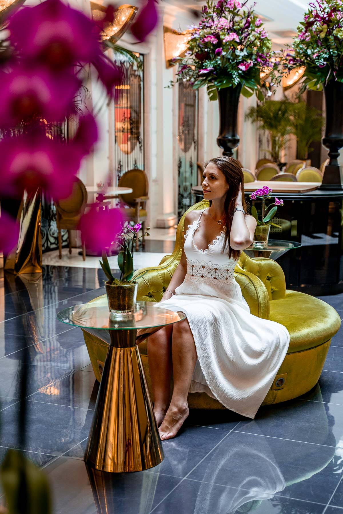 Girl in a white dress sitting in the lobby at the Aria Hotel in Budapest