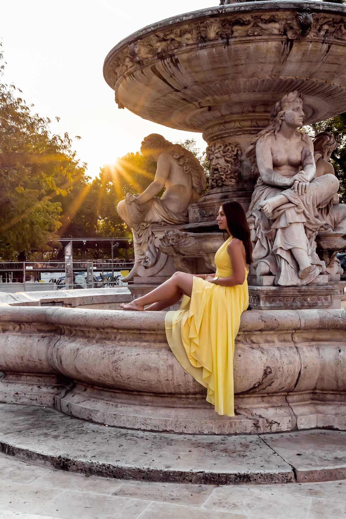 Girl in a yellow dress sitting on the Danubius Fountain in Budapest
