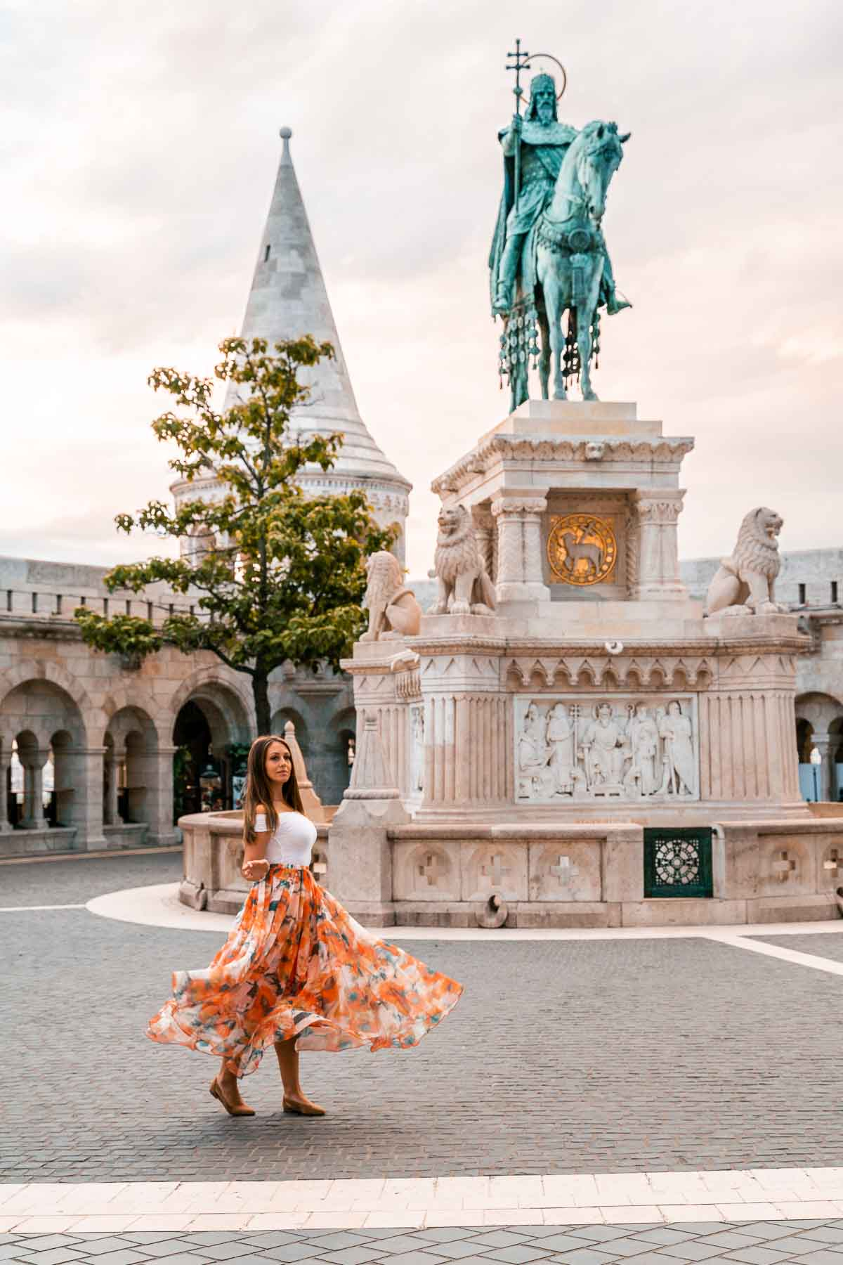 Girl in an orange skirt twirling in front of a statue at Fisherman's Bastion in Budapest