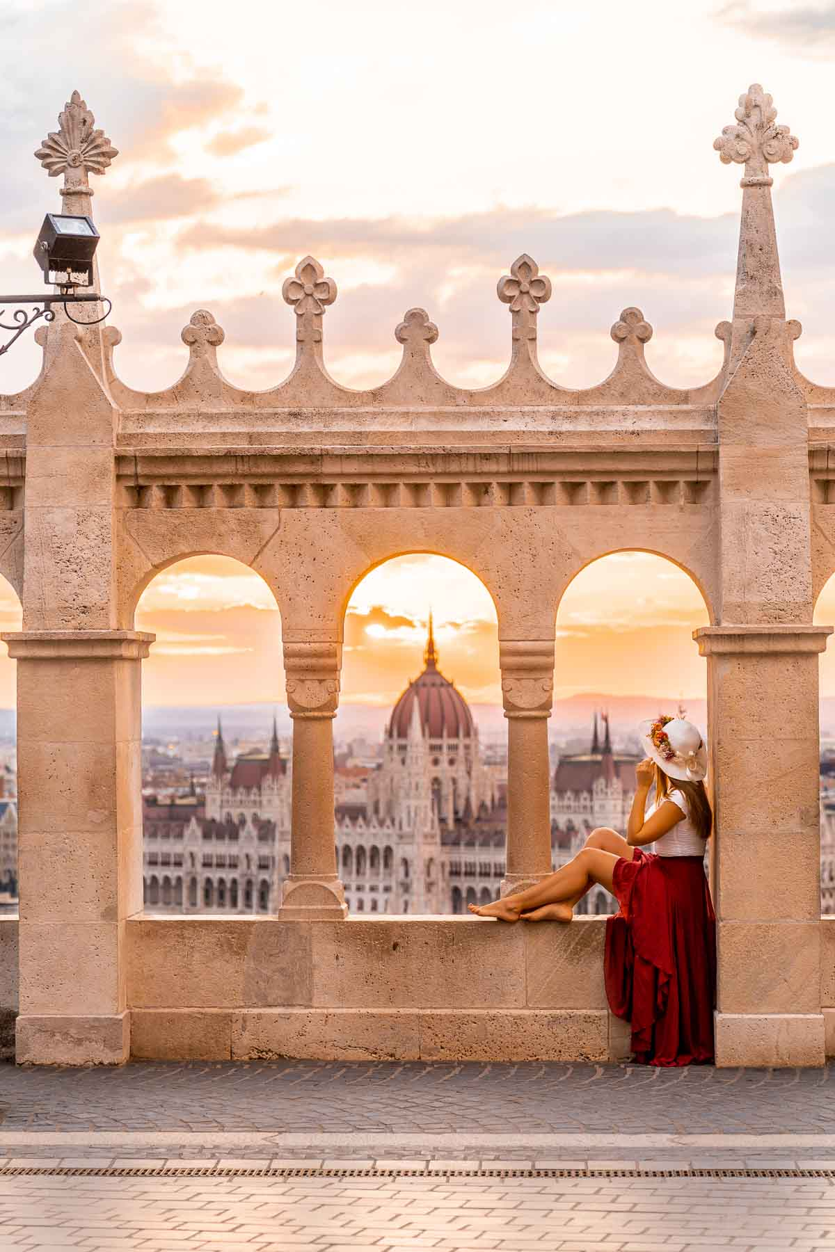 Girl in a red dress sitting at a viewpoint at the Fisherman's Bastion, looking at the Hungarian Parliament at sunrise