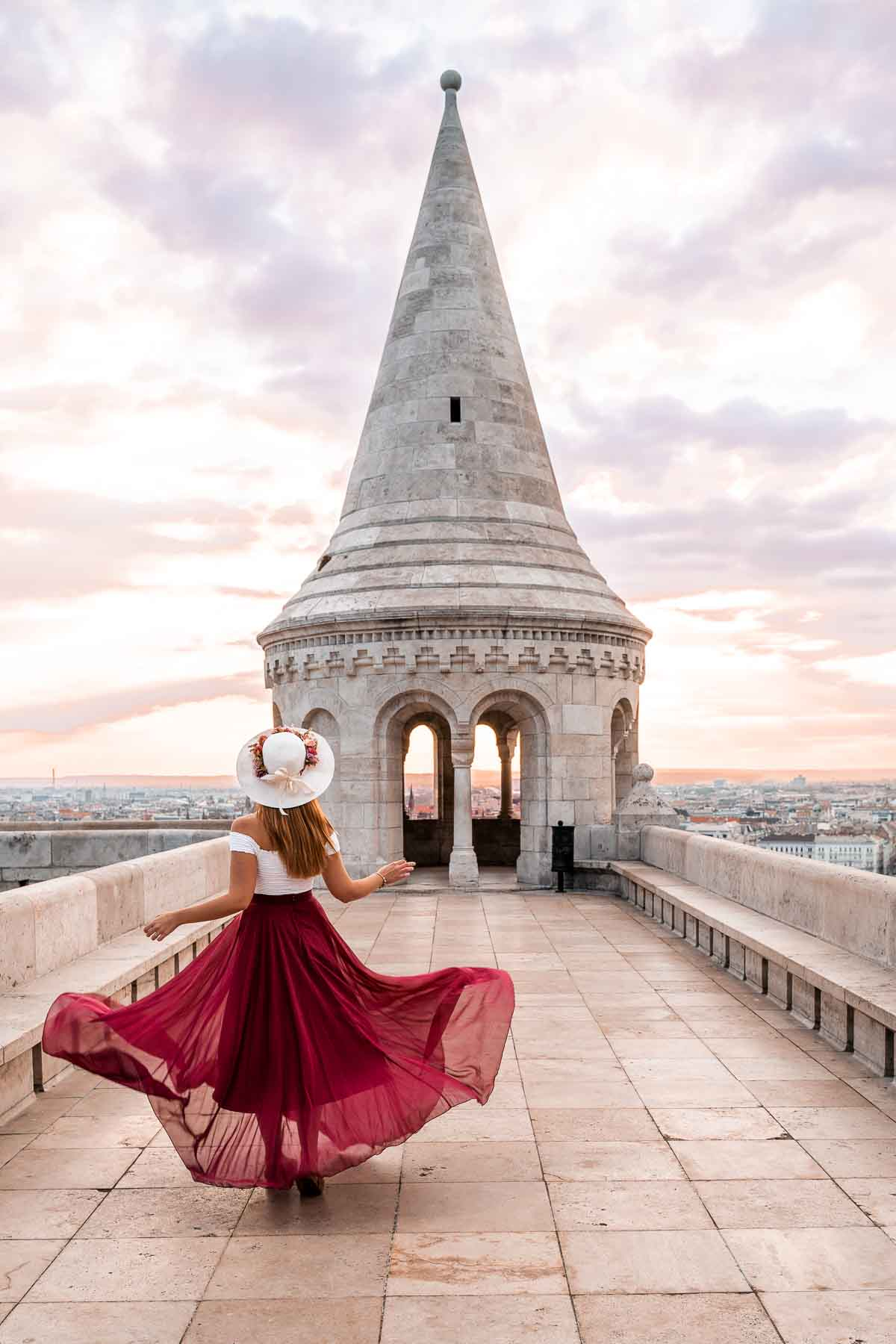 Girl in a red skirt twirling at the upper turrets in Fisherman's Bastion in Budapest