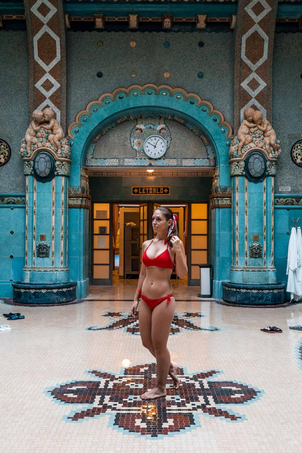 Girl in a red bikini standing in the Gellert Baths in Budapest