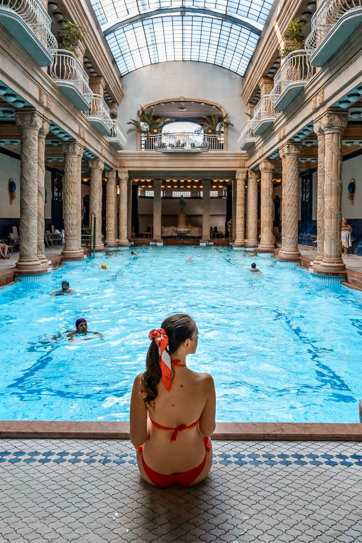 Girl in a red bikini sitting in front of a pool at the Gellert Baths in Budapest