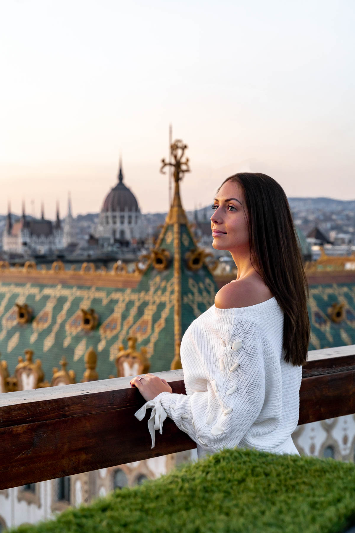 Girl in a white sweater standing at the Intermezzo Roof Terrace with the Hungarian Parliament in the background