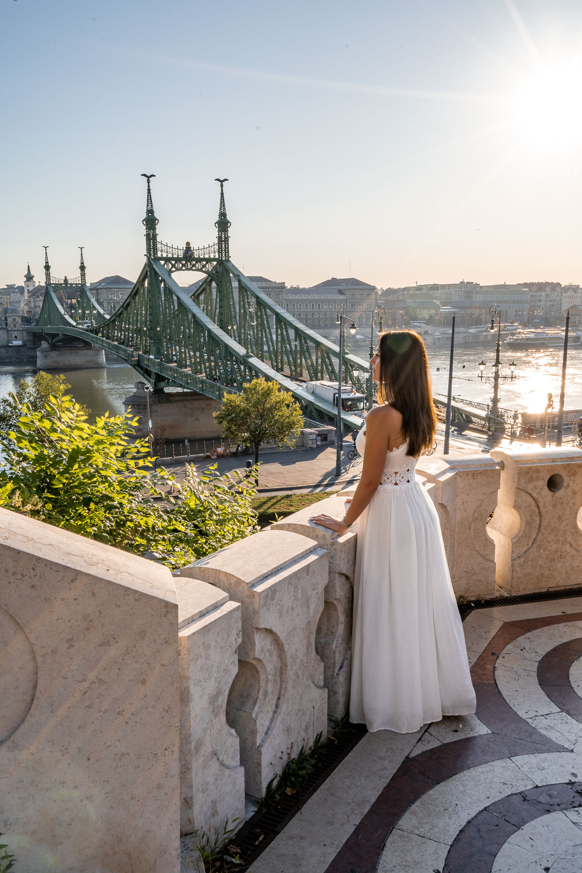 Girl in a white dress standing in front of the Gellért Hill Cave, looking down at the Liberty Bridge in Budapest