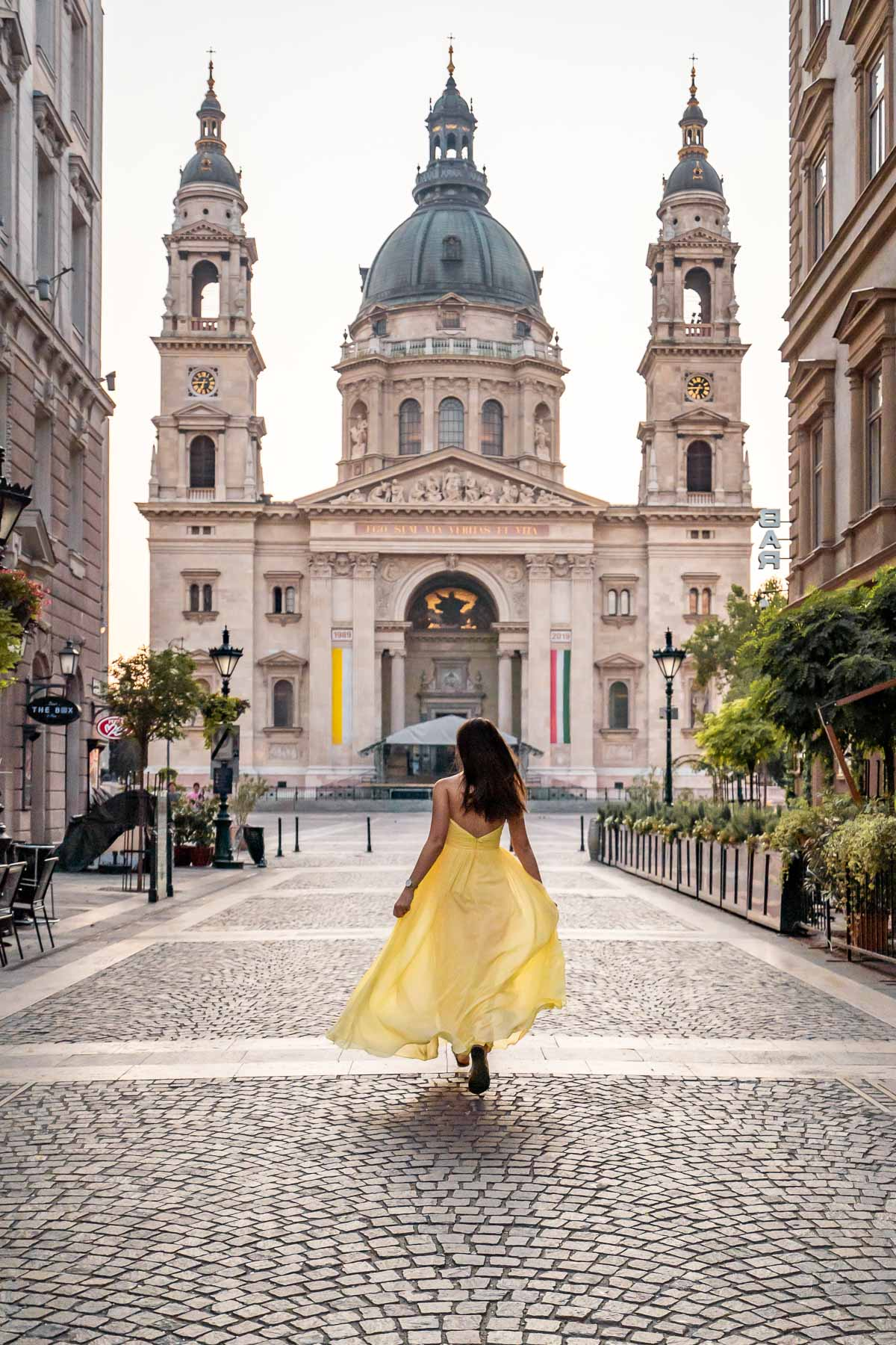 Girl in a yellow dress running towards the St. Stephen's Basilica in Budapest