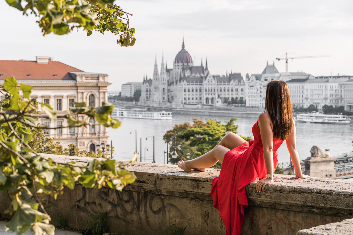 Girl in a red dress sitting on a wall with the Hungarian Parliament in the background