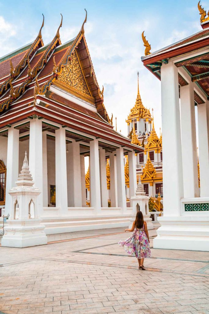 Girl in a purple dress standing in front of the Loha Prasat