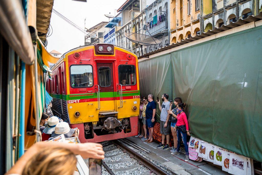 The train is coming at the Maeklong Railway Market
