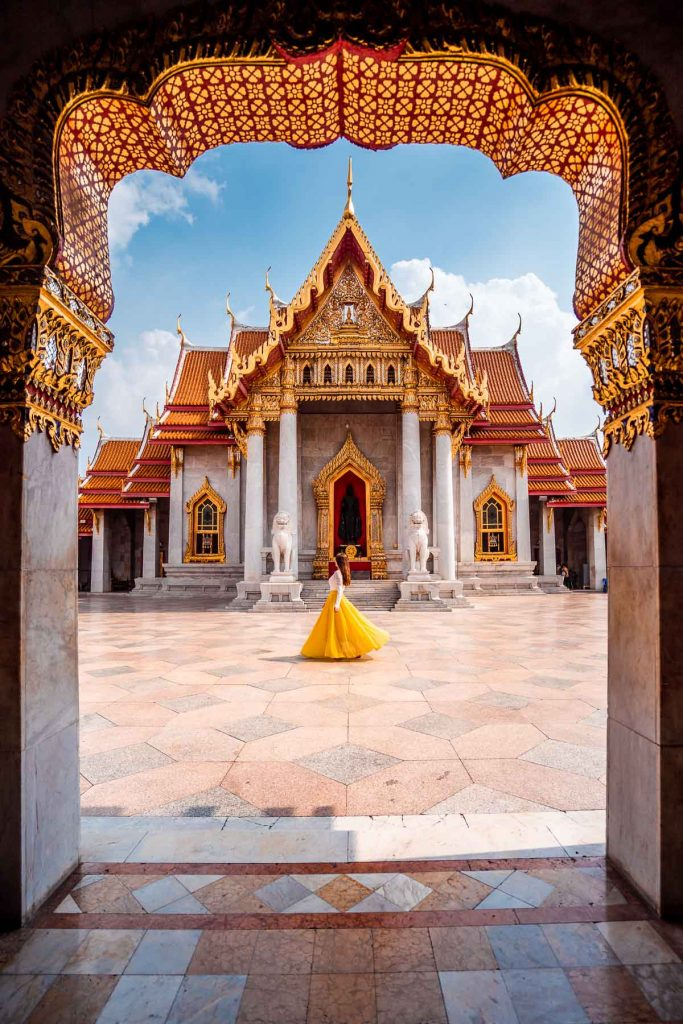 Girl in a yellow dress twirling in front of the Wat Benchamabophit in Bangkok