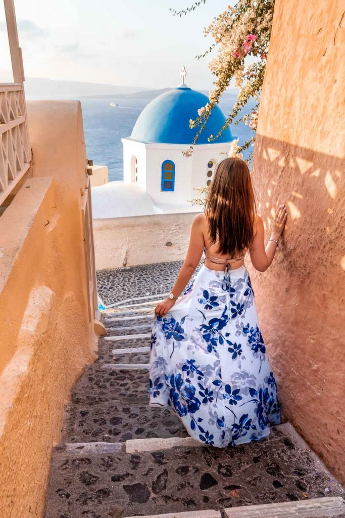Girl in a blue floral dress walking down the stairs with a blue dome in front of her in Oia, Santorini