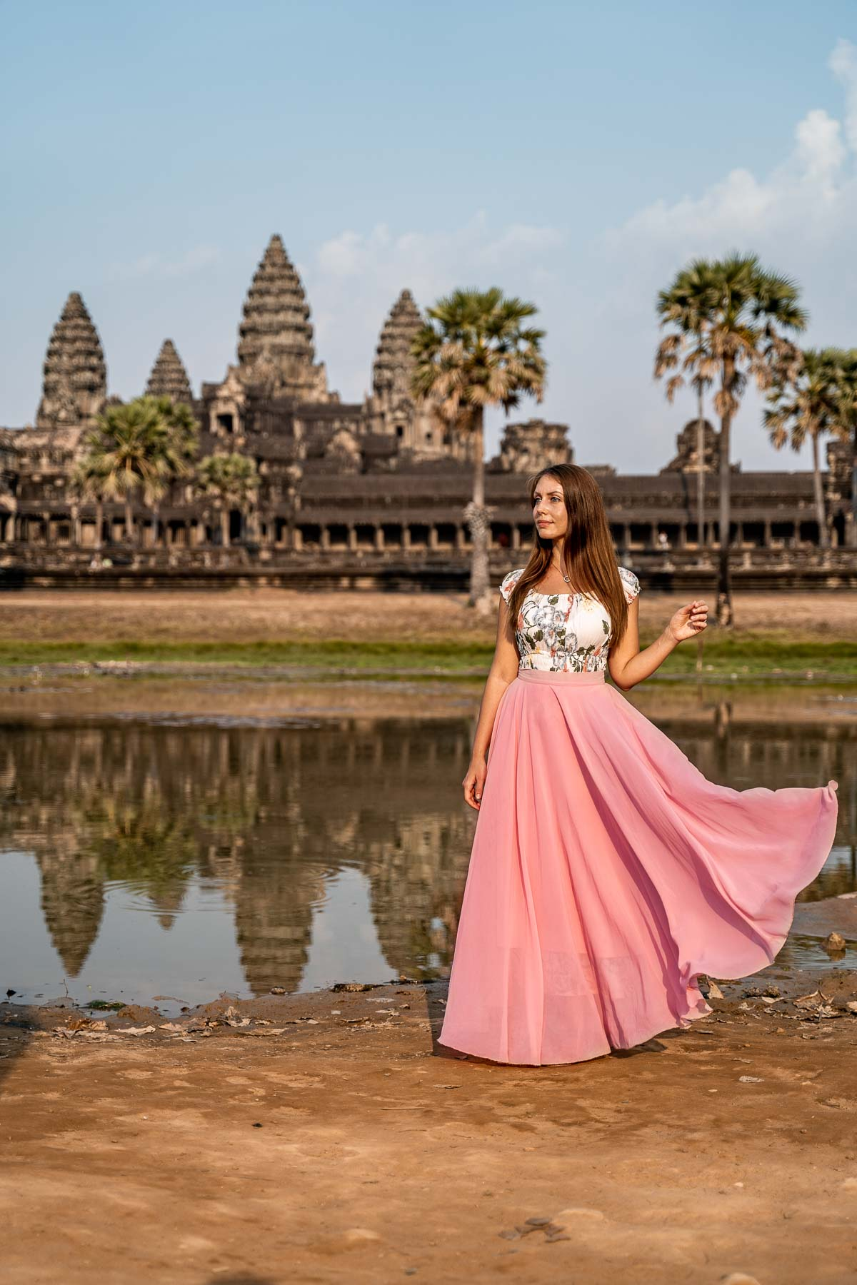 Girl in a pink skirt standing in front of the Angkor Wat in Cambodia