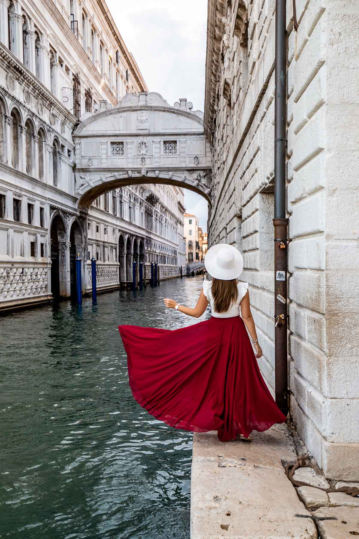 Girl in a red skirt standing below the Bridge of Sighs in Venice, Italy