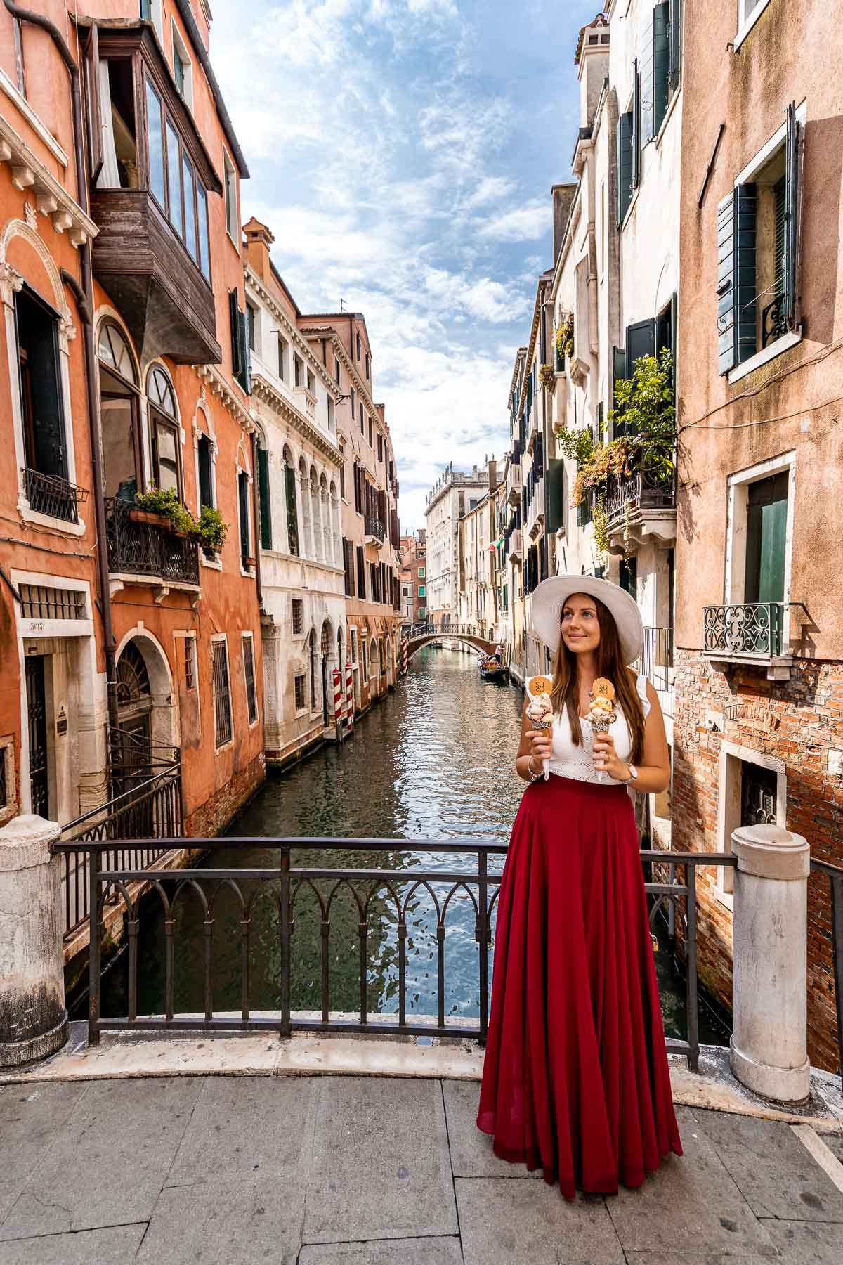 Girl in a red skirt standing on a bridge in Venice with gelatos on her hand