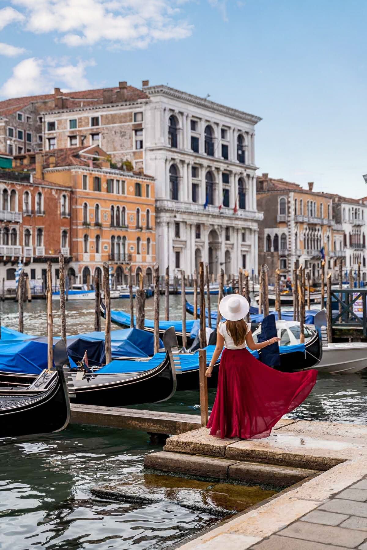 Girl in a red skirt standing in front of the gondolas along the Grand Canal in Venice, Italy