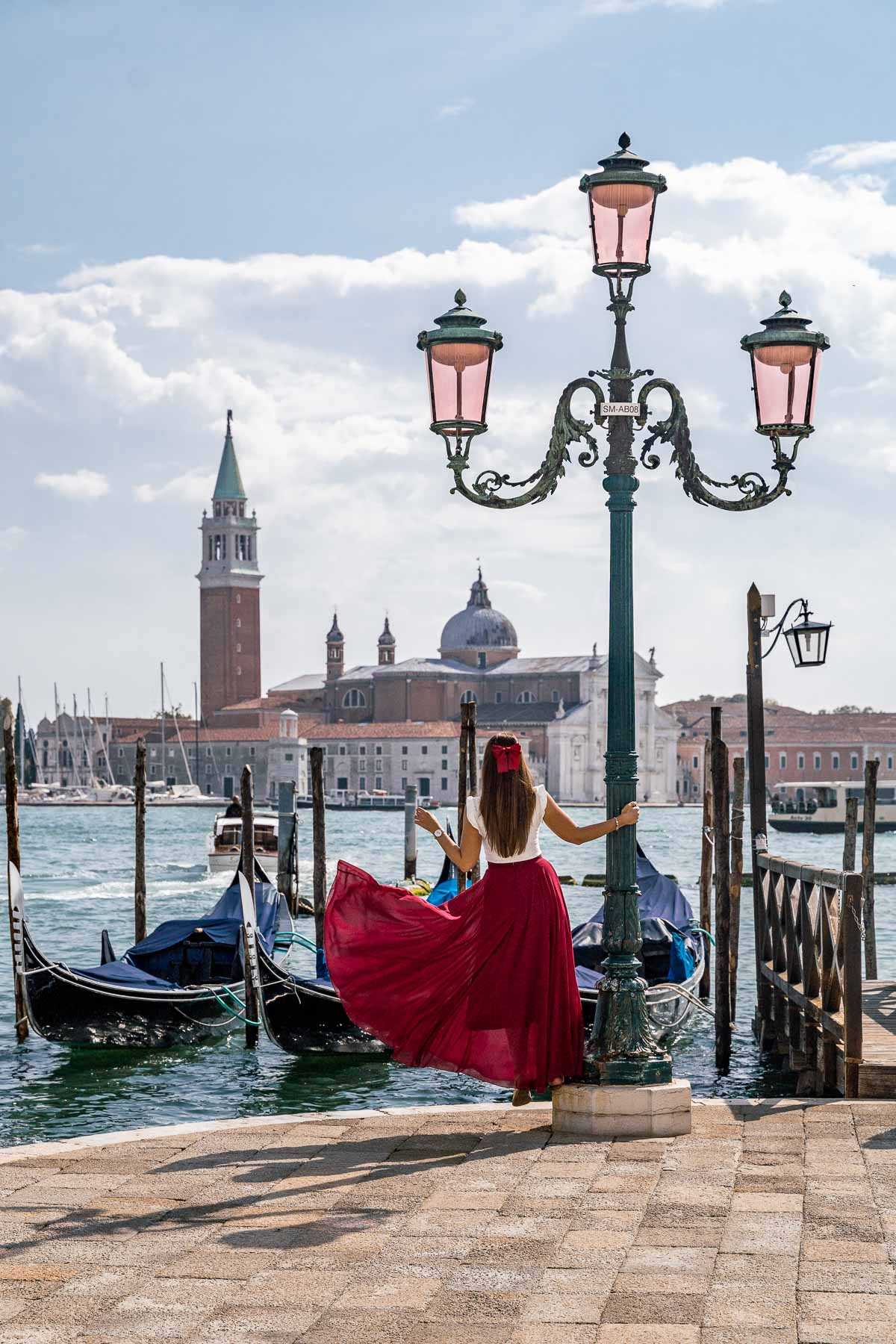 Girl in a red dress standing in front of the Gondolas at St. Mark's Square in Venice, Italy