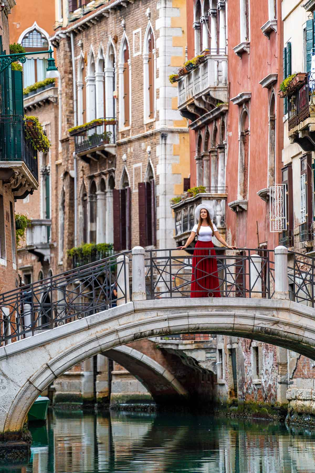 Girl in a red skirt standing on a bridge over the canals of Venice