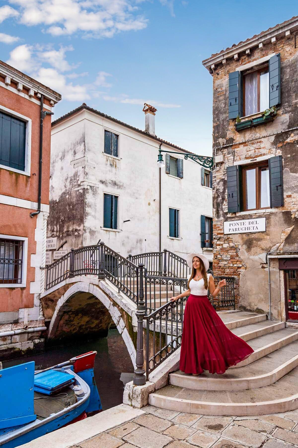 Girl in a red skirt standing on Ponte Del Parucheta in Venice
