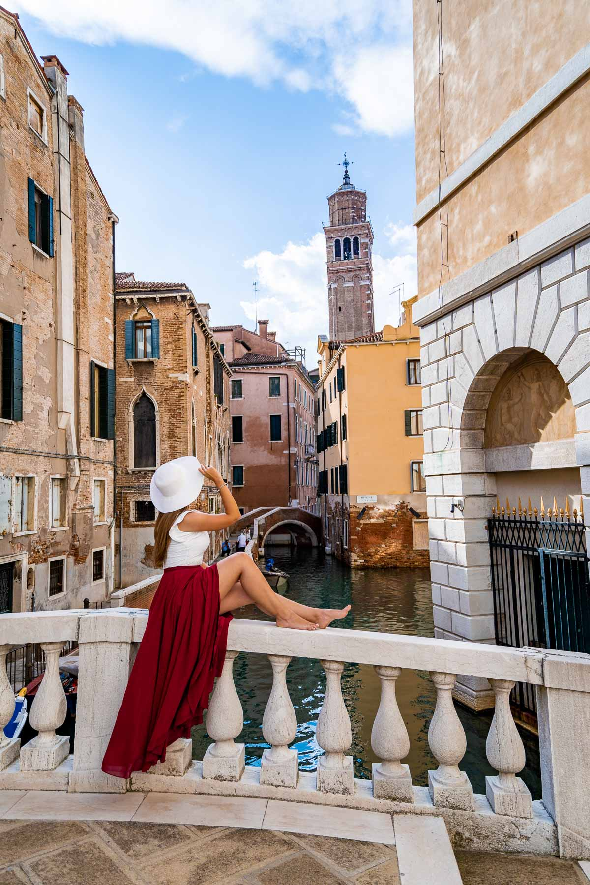 Girl in a red skirt sitting on Ponte Maria Callas in Venice