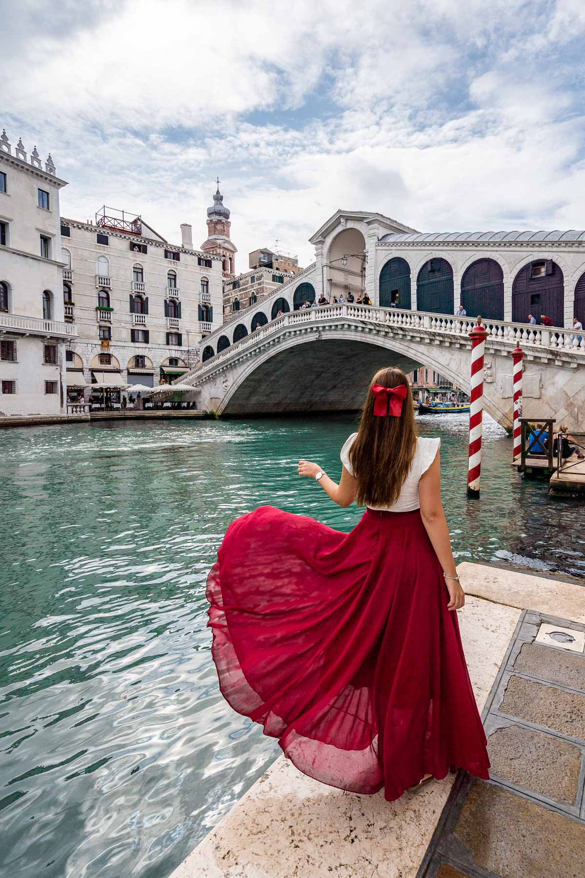 Girl in a red dress twirling in front of Rialto Bridge, which is one of the best Venice Instagram spots