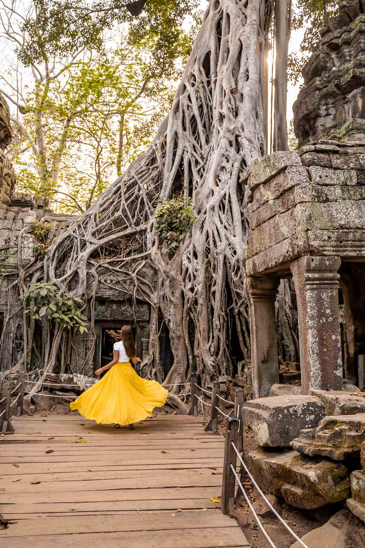 Girl in a yellow skirt twirling in Ta Prohm Temple in Cambodia