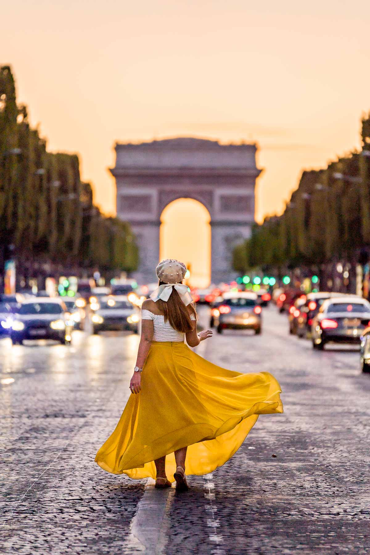Girl in a yellow skirt standing in front of the Arc de Triomphe at the sunset