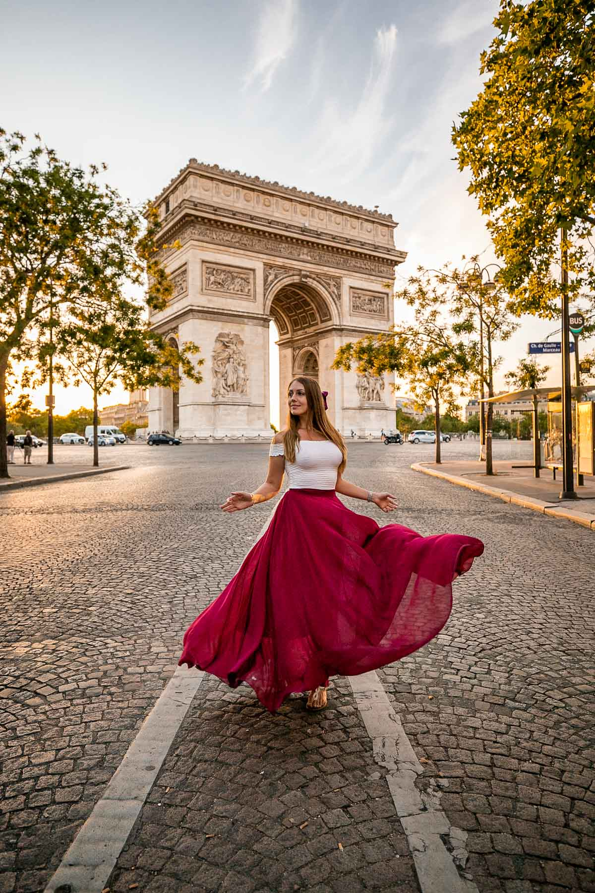 Girl in a red skirt twirling in front of Arc de Triomphe, one of the best Paris Instagram Spots