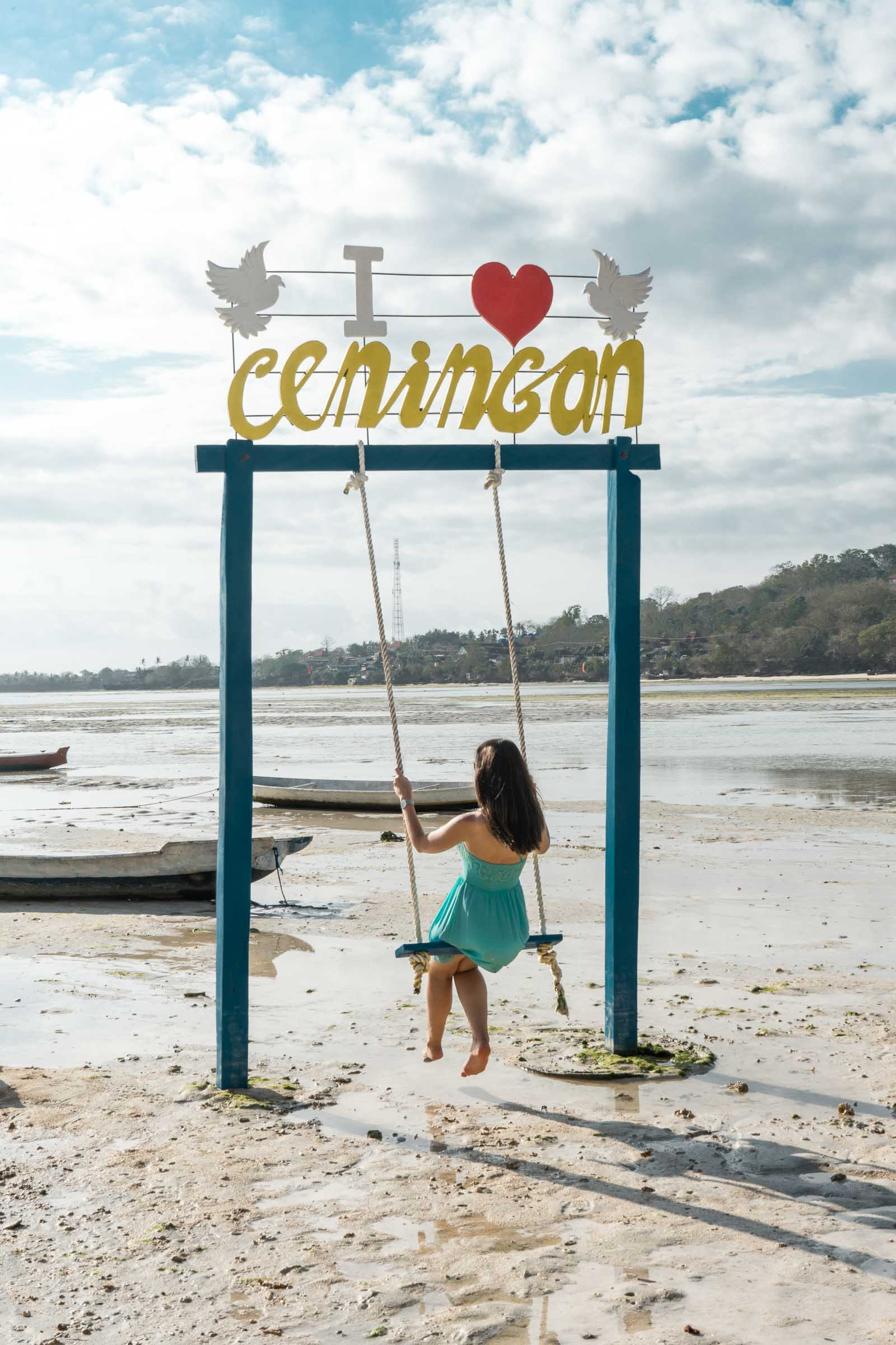 Girl in a blue dress sitting on a swing at a beach on Nusa Ceningan