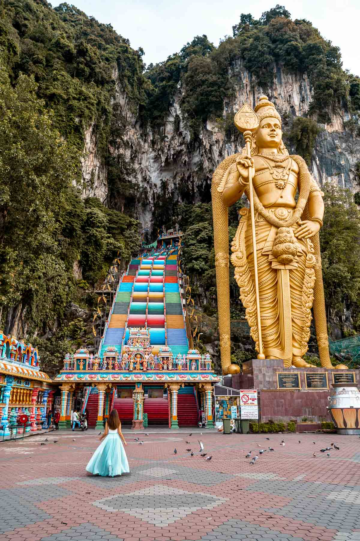 Girl in a blue dress standing in front of the colorful stairs at Batu Caves, Kuala Lumpur