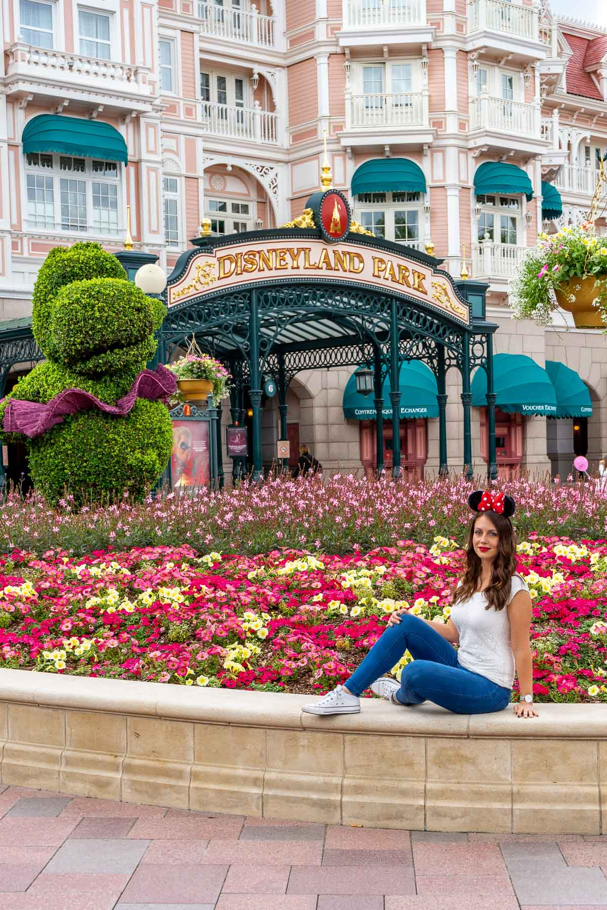 Girl sitting in front of the entrance of Disneyland Paris