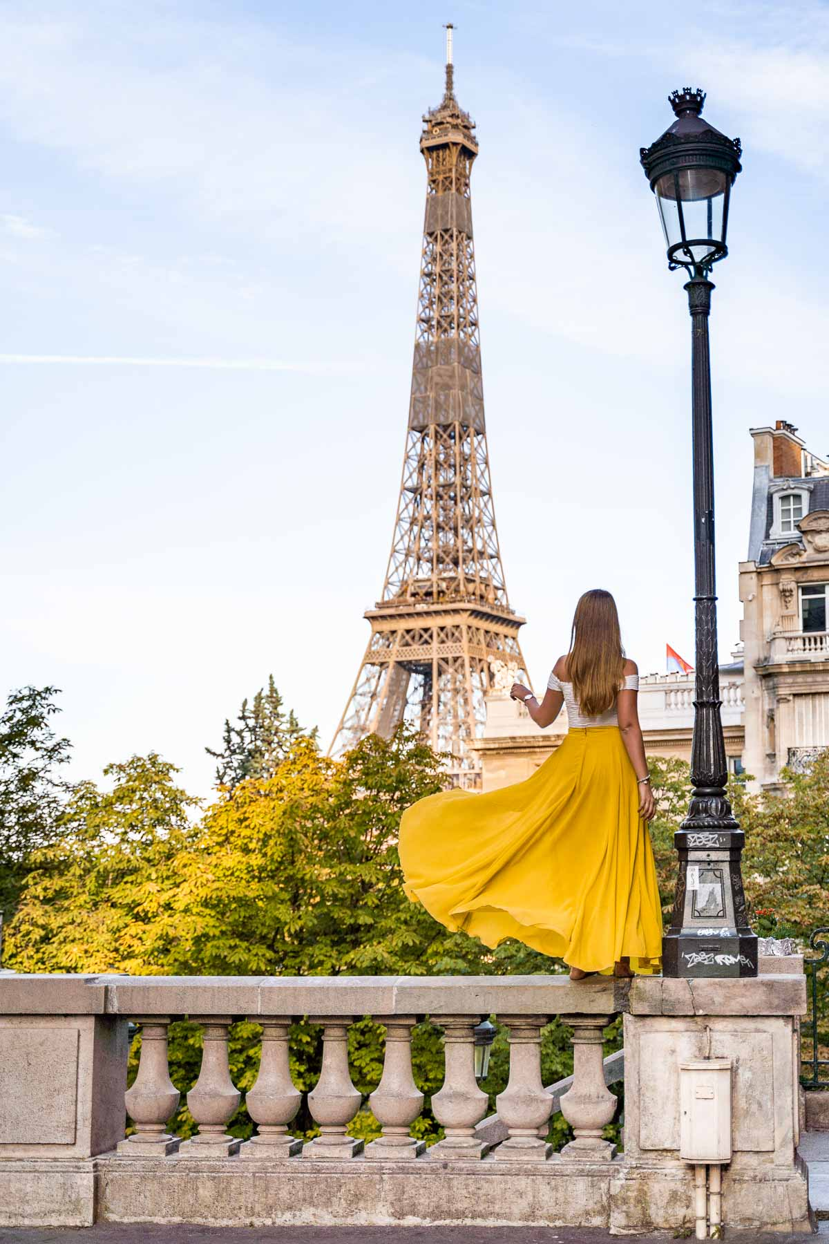 Girl in a yellow skirt twirling in front of the Eiffel Tower at Avenue de Camoens, Paris