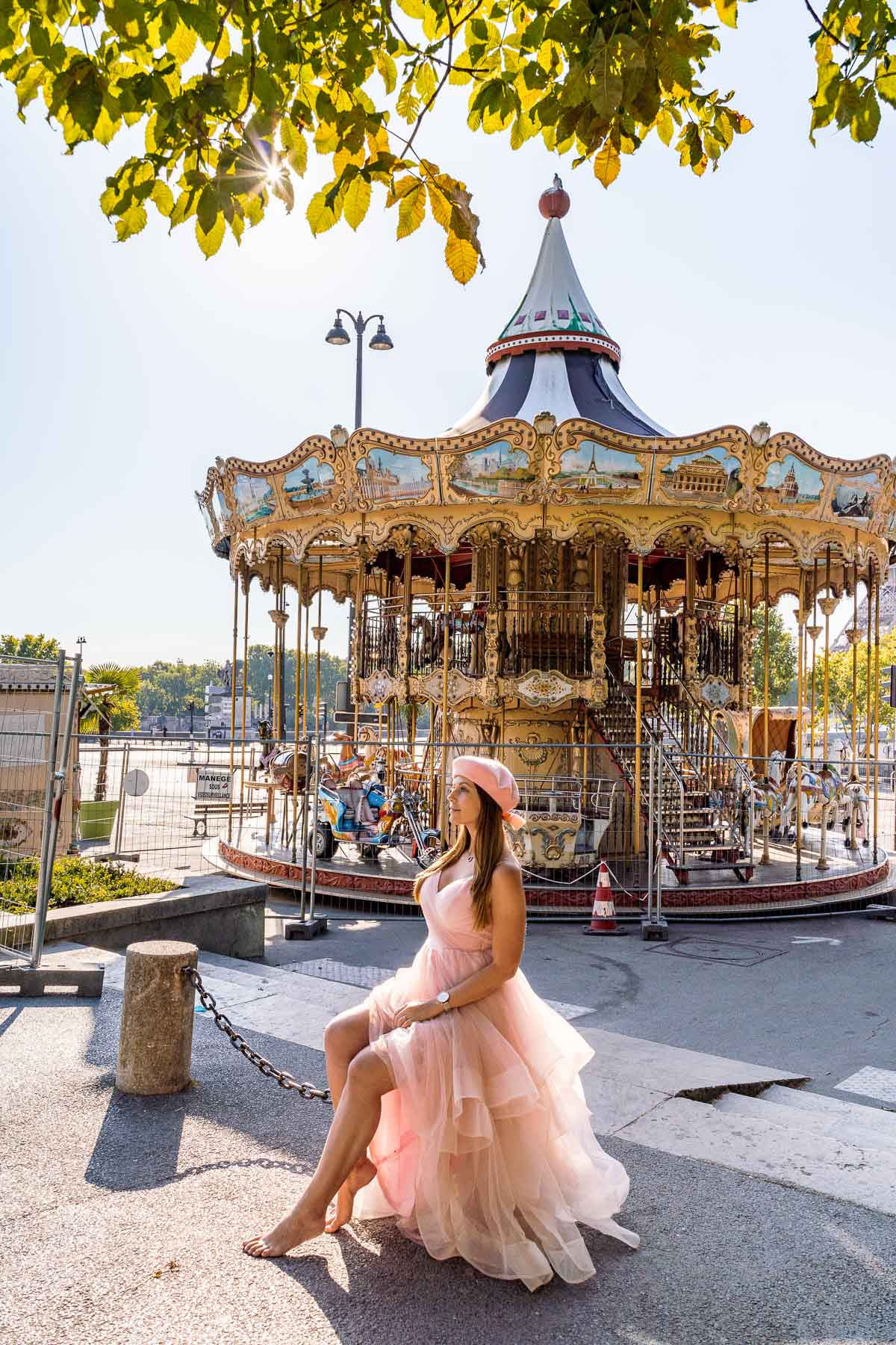 Girl in a pink dress sitting in front of a carousel near Trocadero in Paris