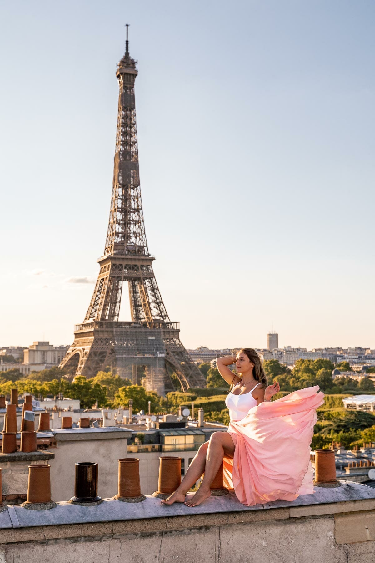 Girl in a pink skirt sitting on a rooftop in Paris with the Eiffel Tower in the background