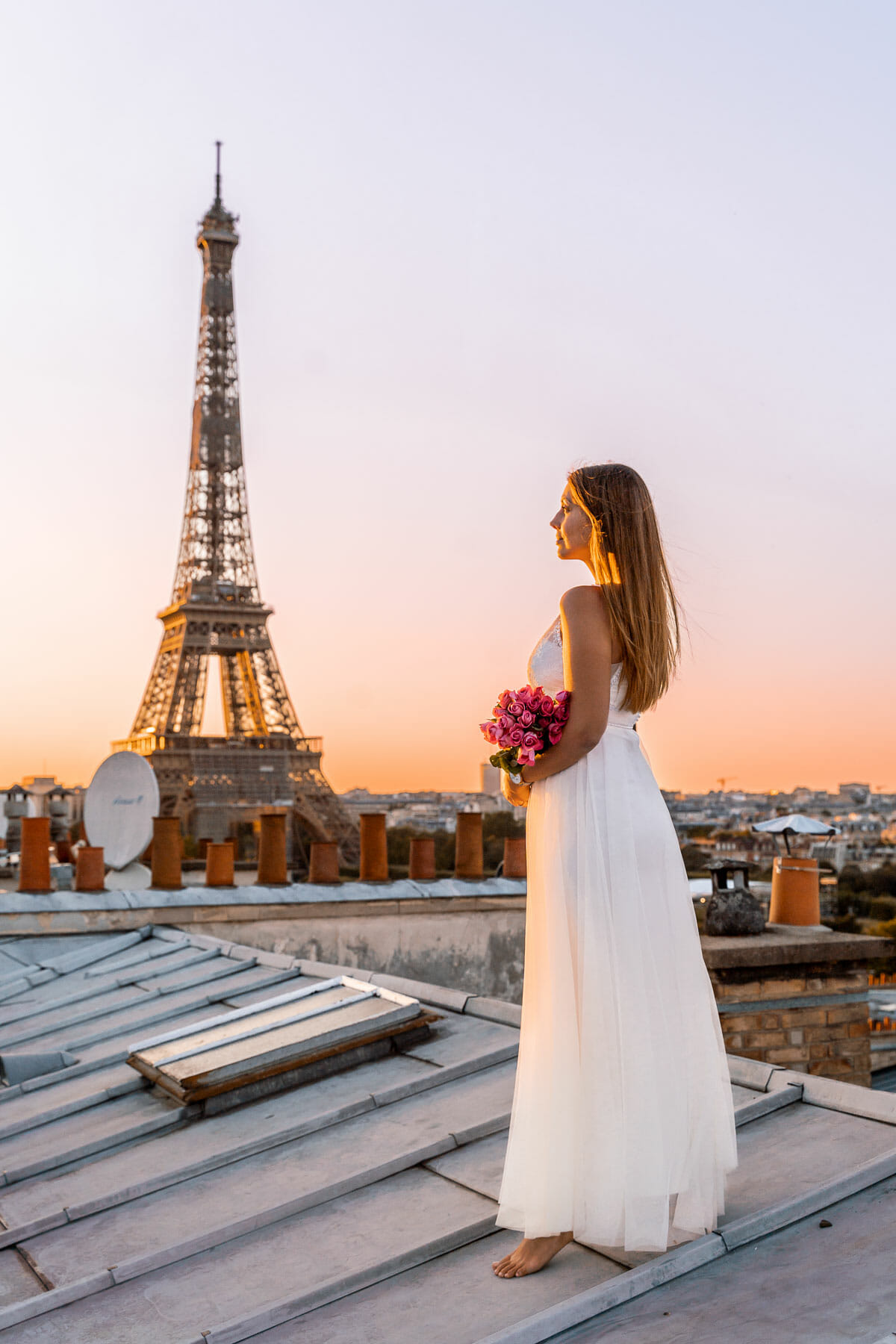 Girl in a white dress standing on a rooftop in Paris, looking at the Eiffel Tower