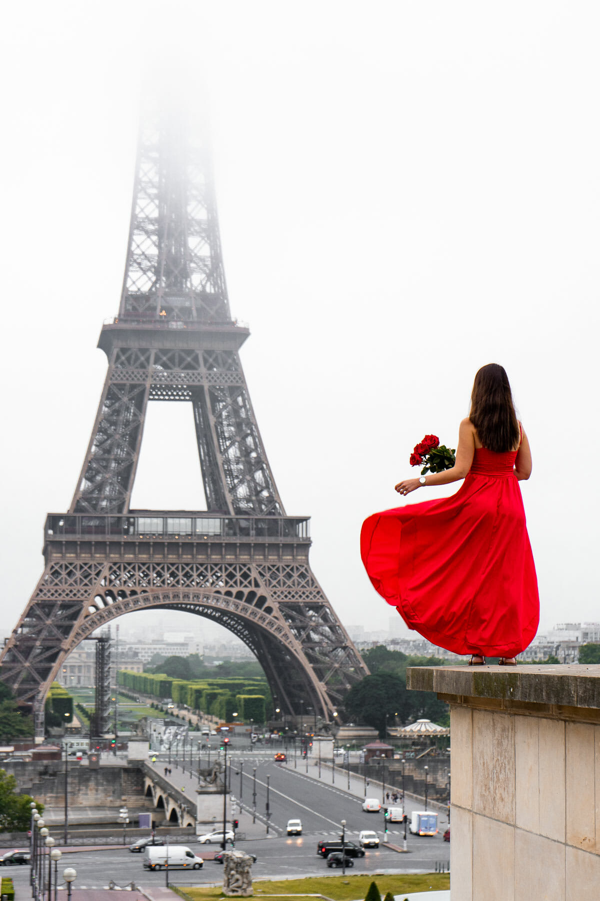 Girl in a red dress standing at Trocadero looking at the Eiffel Tower