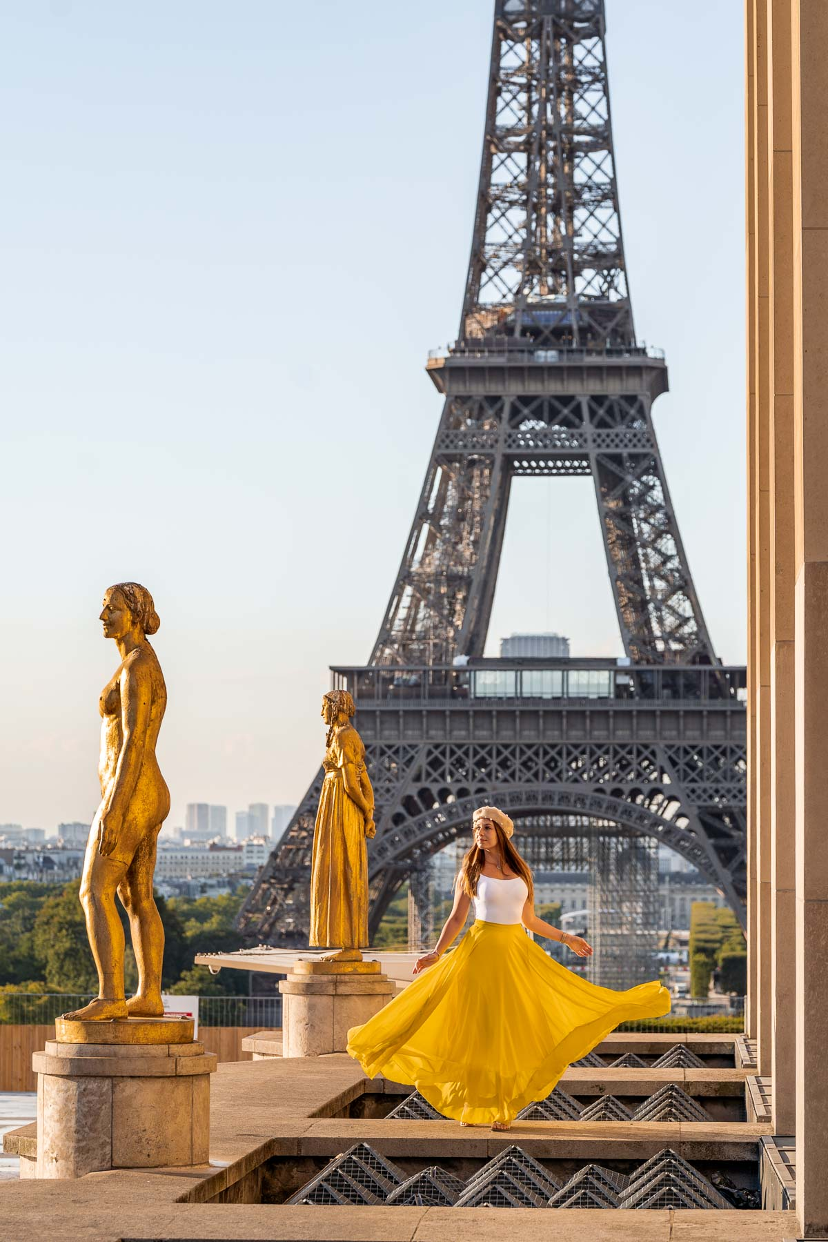 Girl in a yellow dress twirling in front of the Eiffel Tower at Trocadero, one of the most instagrammable places in Paris