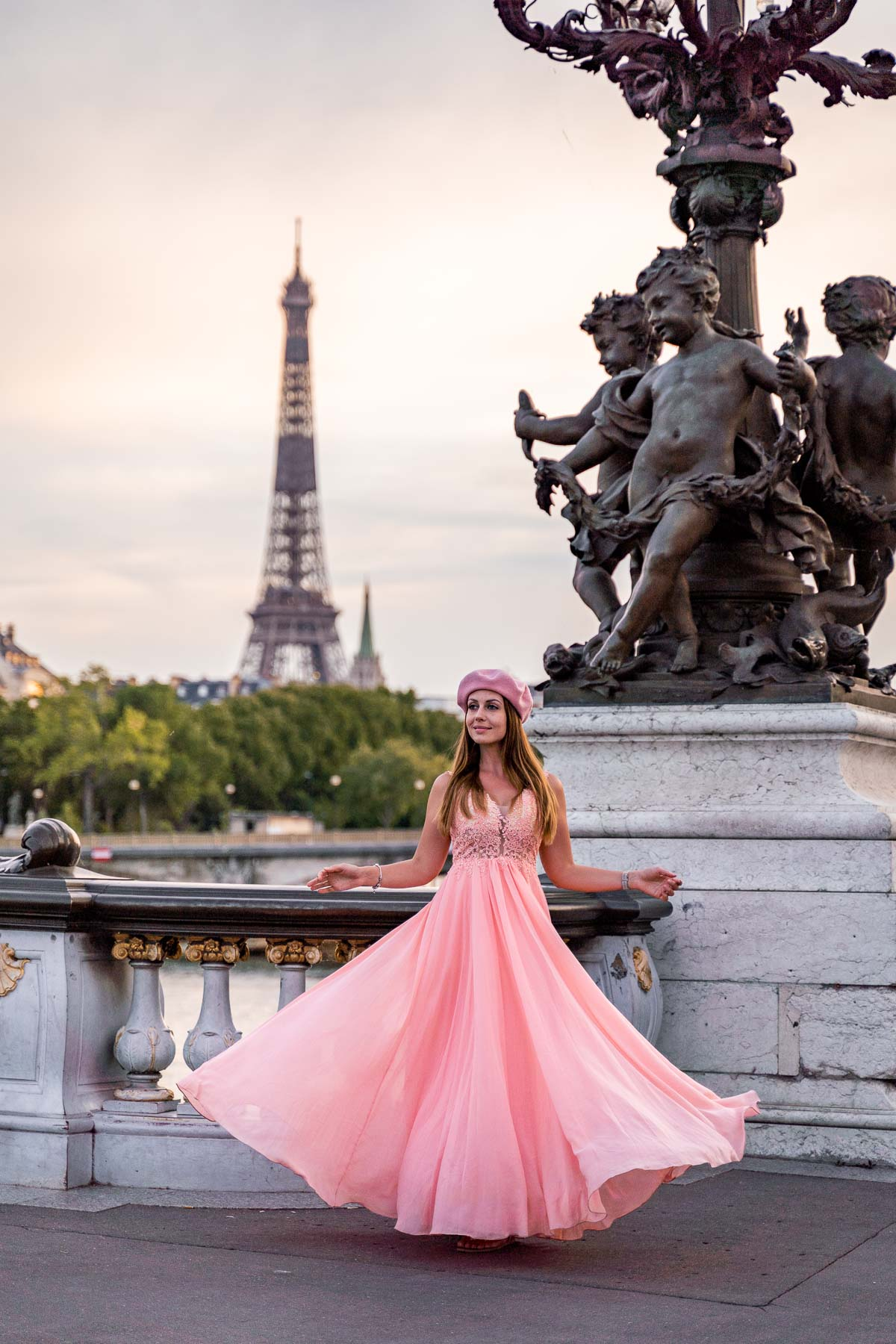 Girl in a pink dress twirling on Pont Alexandre III with the Eiffel Tower in the background