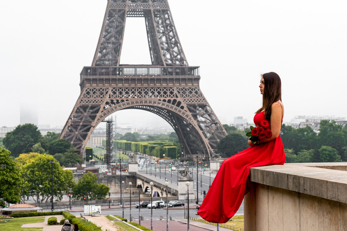 Girl in a red dress sitting at Trocadero in front of the Eiffel Tower