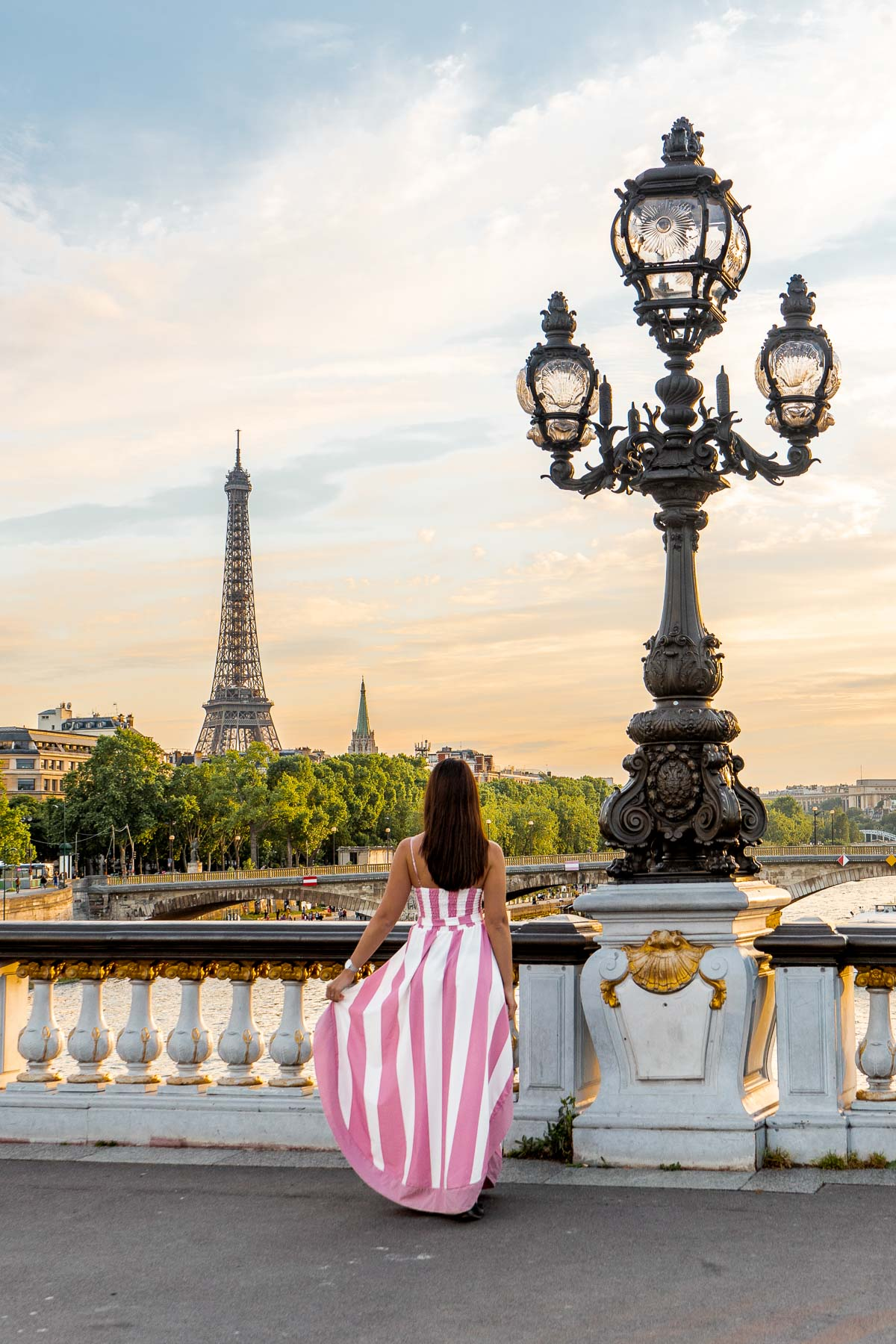 Girl in a pink-white dress standing on Pont Alexandre III, watching the sunset behind the Eiffel Tower