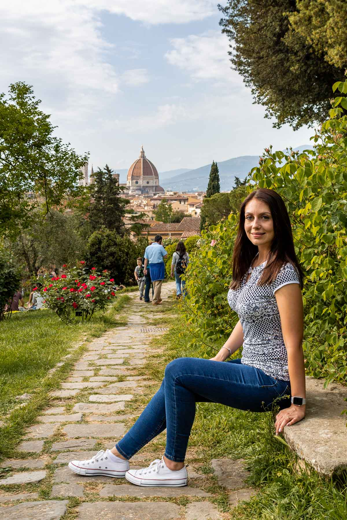 Girl sitting on a bench in Giardino delle Rose in Florence, Italy