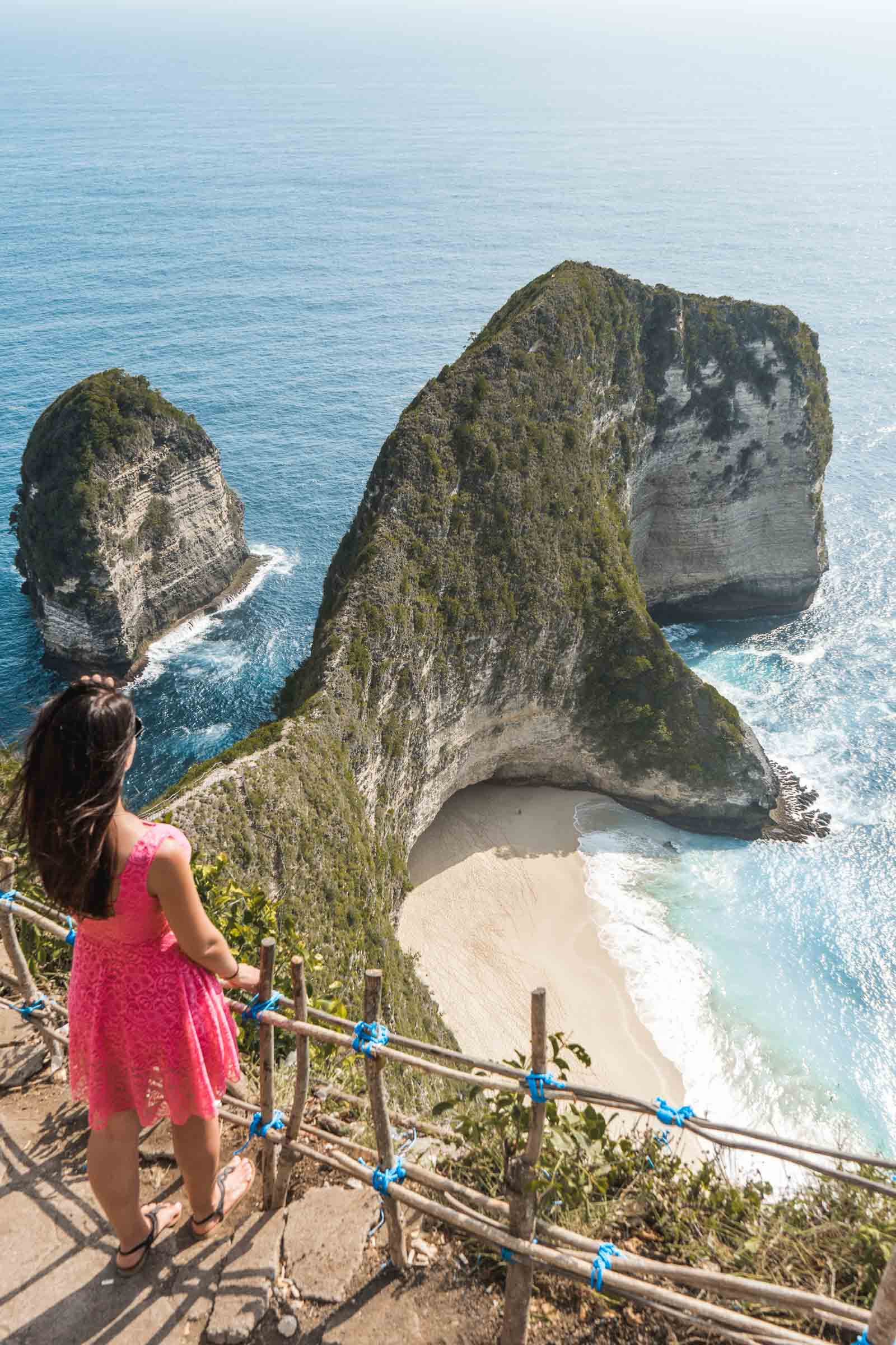 Girl in a pink dress looking at Kelinking Beach in Nusa Penida