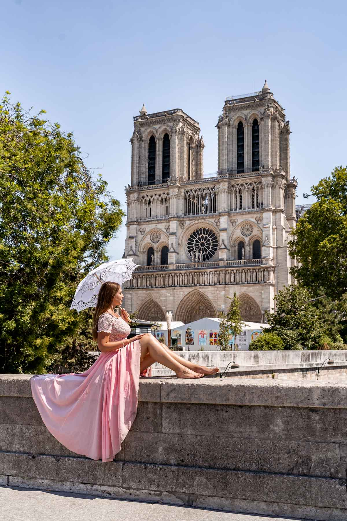 Girl in a pink skirt sitting in front of the Notre Dame, one of the most instagrammable places in Paris