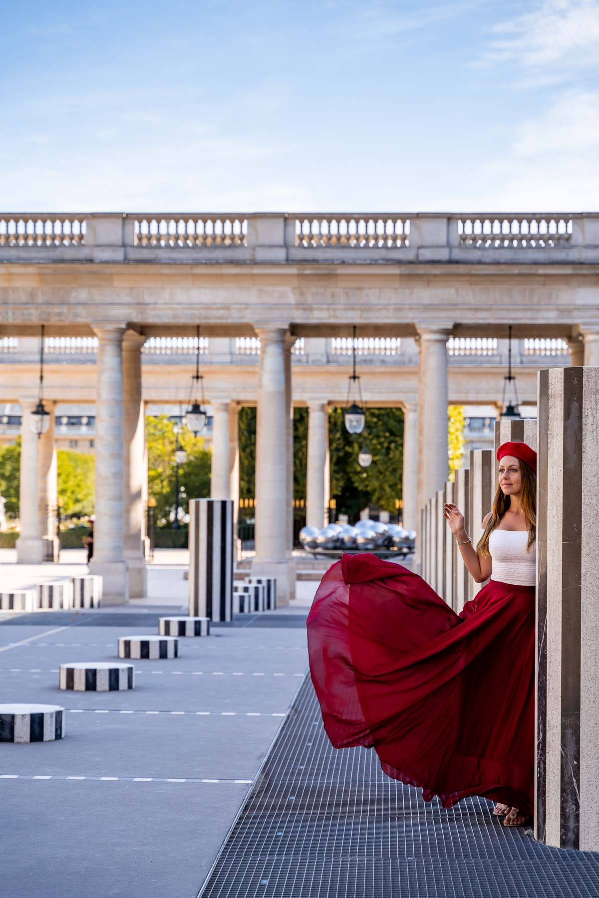Girl in a red dress standing in Palais Royal, one of the most instagrammable places in Paris