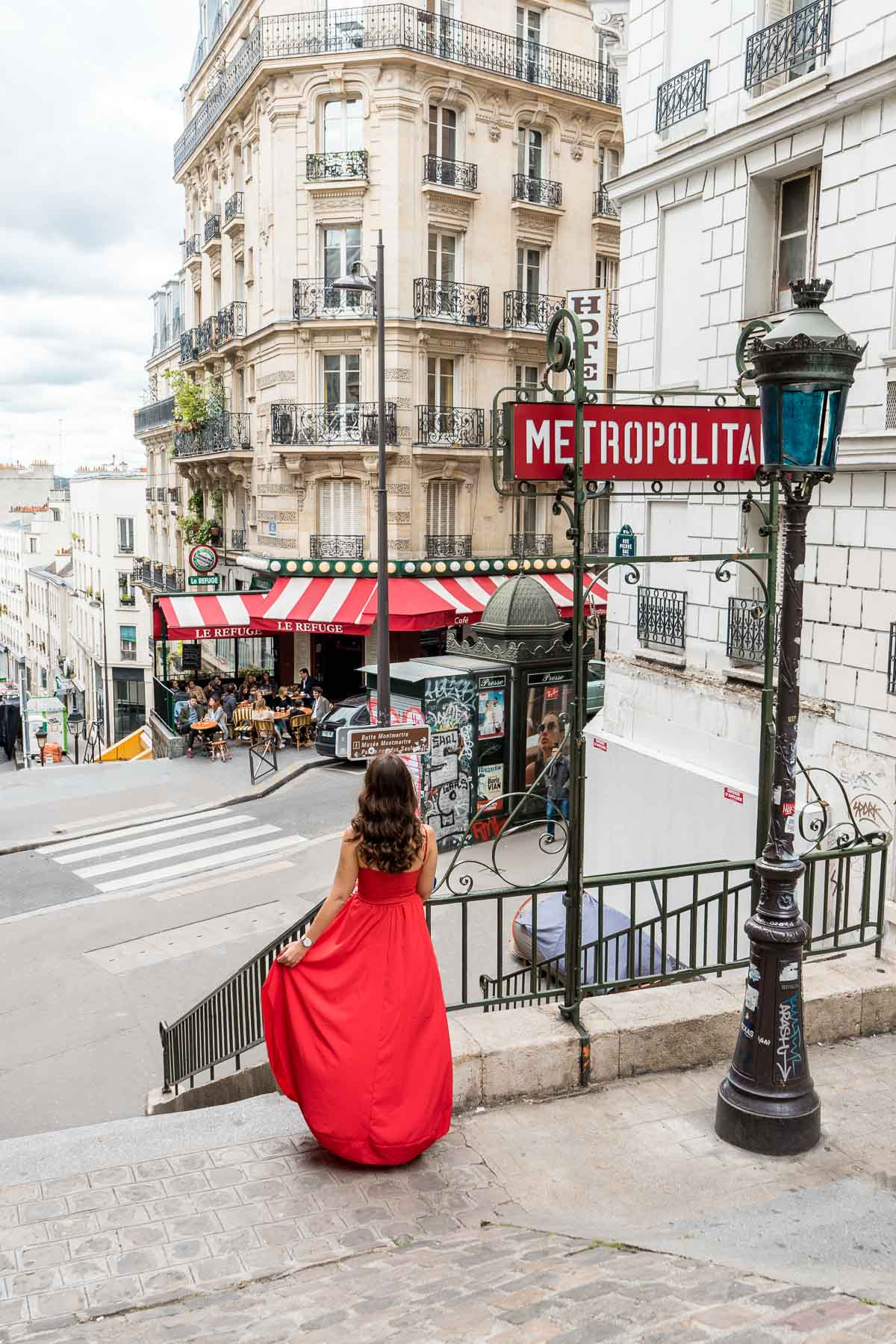 Girl in a red dress standing in front of a metro station in Paris