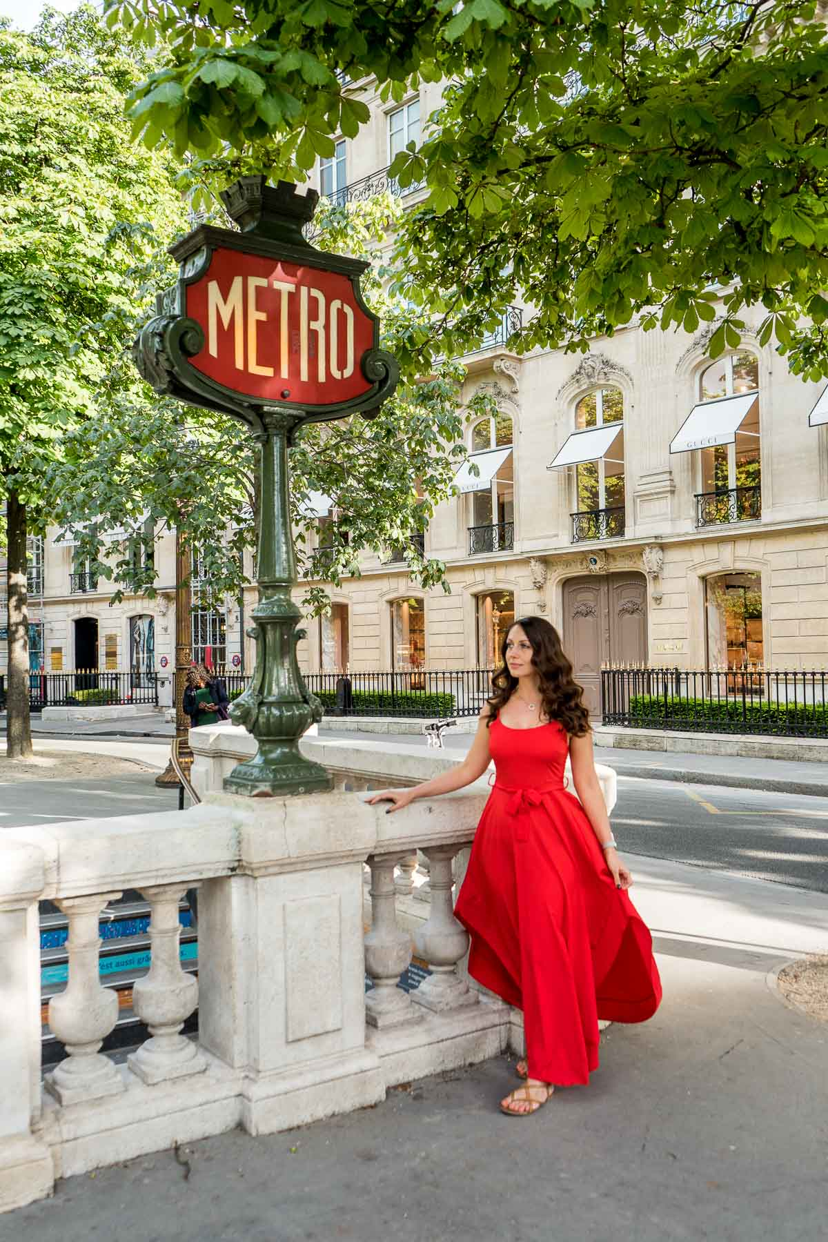 Girl in a red dress standing at a metro station sign in Paris, France