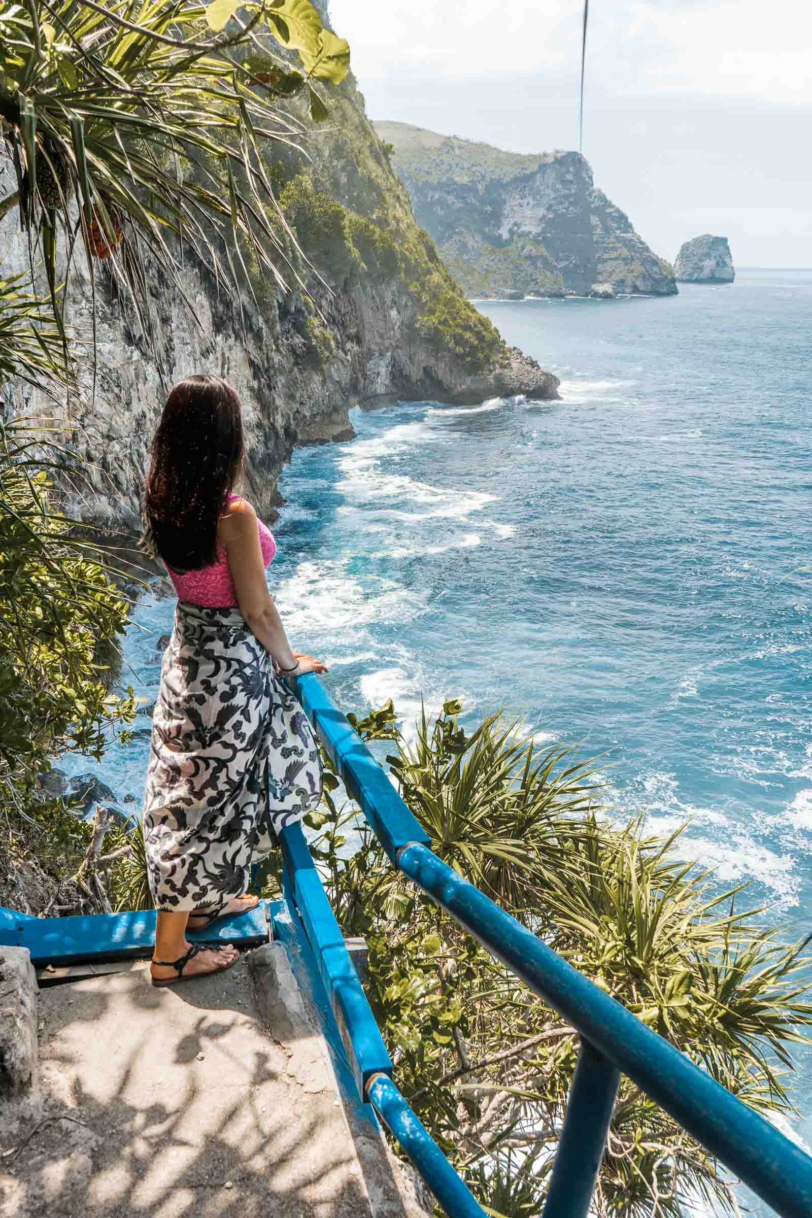 Girl in a pink dress looking at the view at Peguyangan Waterfall, Nusa Penida