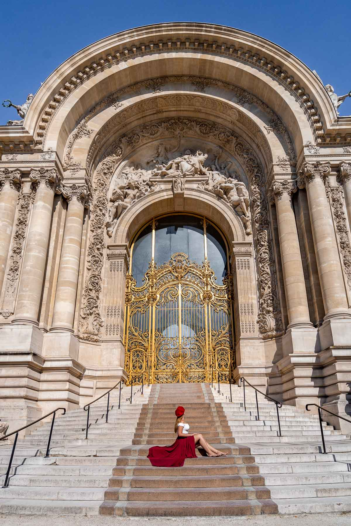 Girl in a red skirt sitting in front of Petit Palais in Paris