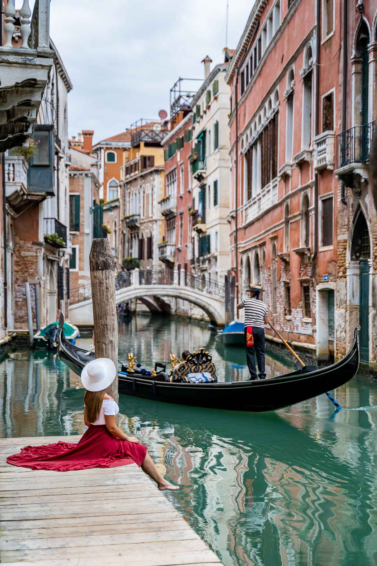 Girl in a red skirt sitting on a little pier along the canals, which is one of the best Venice Instagram spots
